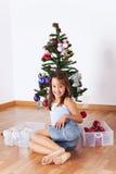 Liten flicka som dekorerar en jultree Arkivbild