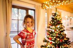 Liten flicka som dekorerar julgranen tilltrasslad i chain ljus Arkivbilder