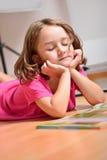 Liten flicka som drömmer, medan läsa en bok Arkivbild