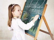 Liten flicka som drar en bild med krita på svart tavla fotografering för bildbyråer