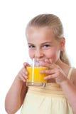 Liten flicka som dricker ett exponeringsglas av orange fruktsaft Arkivbild