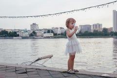Liten flicka som dricker ett exponeringsglas av vatten Arkivfoton