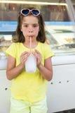 Liten flicka som dricker ett med is royaltyfria bilder