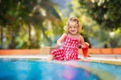 Liten flicka som dricker fruktsaft på en simbassäng royaltyfri fotografi
