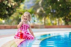 Liten flicka som dricker fruktsaft på en simbassäng royaltyfria bilder