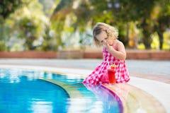 Liten flicka som dricker fruktsaft på en simbassäng royaltyfri foto