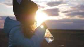 Liten flicka som dricker sötvatten från den plast- flaskan med solnedgångbakgrund Att att släcka törstat ditt lager videofilmer