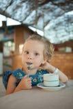 Liten flicka som dricker te från en kopp Royaltyfri Fotografi