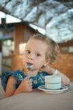 Liten flicka som dricker te från en kopp Arkivfoto