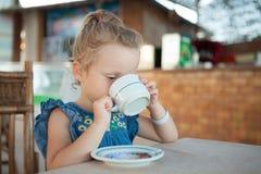 Liten flicka som dricker te från en kopp Royaltyfri Bild