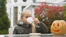 Liten flicka som dricker te som ler till pumpastålar-nolla-lyktan, lek på allhelgonaaftonen arkivfilmer