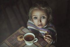 Liten flicka som dricker te med kex arkivfoton