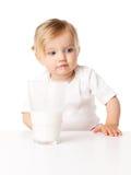Liten flickadrinkar mjölkar arkivfoton