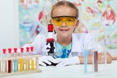 Liten flicka som experimenterar i elementär vetenskapsgrupp Arkivbild
