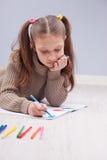 Liten flicka som färgar på hennes anteckningsbok arkivfoto