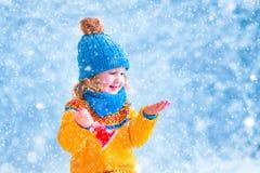 Liten flicka som fångar snöflingor Royaltyfri Foto