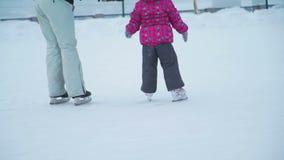 Liten flicka som för första gången åker skridskor med mamman arkivfilmer
