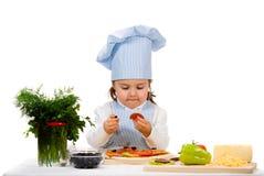 Liten flicka som förbereder en pizza royaltyfri bild