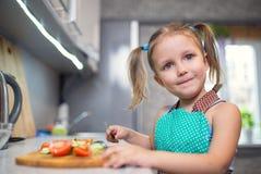 Liten flicka som förbereder sallad i köket fotografering för bildbyråer