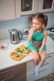 Liten flicka som förbereder sallad i köket arkivbilder