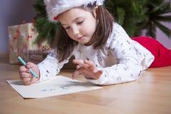 Liten flicka som förbereder Santa Letter Henne som målar gåvorna s Arkivfoto