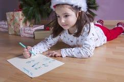 Liten flicka som förbereder Santa Letter Henne som målar gåvorna s Royaltyfri Foto