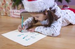 Liten flicka som förbereder Santa Letter Henne som målar gåvorna s Royaltyfria Bilder