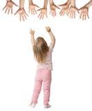 Liten flicka som försöker att nå streched händer royaltyfri foto