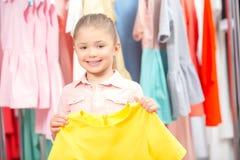 Liten flicka som försöker en ny klänning Royaltyfria Bilder
