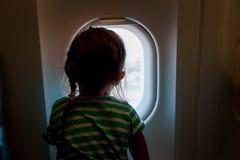 Liten flicka som förutom ser flygplanfönstret Förtjusande resande för liten unge vid ett flygplan Fotografering för Bildbyråer