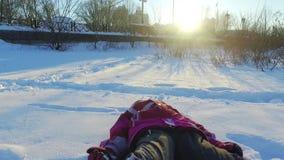 Liten flicka som faller i snö Barn i vinterpark Solig vinterdag arkivfilmer