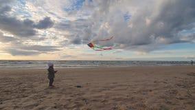 Liten flicka som flyger en drake p? stranden stock video