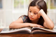Liten flicka som fokuseras på läsning Royaltyfria Bilder
