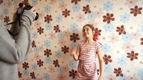 Liten flicka som framme poserar av kameran lager videofilmer