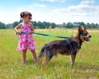 Liten flicka som går med hunden Arkivbild