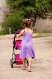 Liten flicka som går med leksaksittvagnen. Liten mamma. Royaltyfri Fotografi