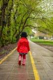 Liten flicka som går på en regnig höstdag arkivbild