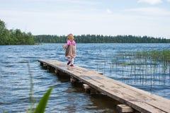 Liten flicka som går på pir på sjön Royaltyfri Foto