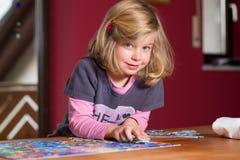 Liten flicka som gör ett pussel Fotografering för Bildbyråer