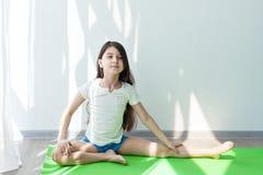 Liten flicka som gör gymnastik på en gräsplan som är matt för yoga Royaltyfri Foto