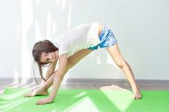 Liten flicka som gör gymnastik på en gräsplan som är matt för yoga Arkivbilder