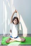 Liten flicka som gör gymnastik på en grön yoga som är matt i lotusblommapositionen Arkivfoton