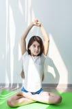 Liten flicka som gör gymnastik på en grön yoga som är matt i lotusblommapositionen Arkivbilder