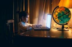 Liten flicka som gör läxa på bärbara datorn på aftonen royaltyfria bilder