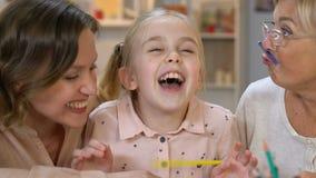 Liten flicka som gör mustaschen med blyertspennan och att ha gyckel med föräldrar, lycka arkivfilmer