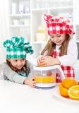 Liten flicka som gör ny orange fruktsaft Royaltyfri Foto