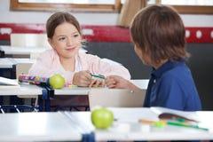 Liten flicka som ger blyertspennan till pojken i klassrum arkivbild
