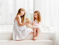 Liten flicka som ger hennes leksak för nallebjörn till äldre syster royaltyfri fotografi