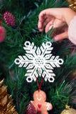 Liten flicka som hänger den dekorativa snöflingan på julträd Fotografering för Bildbyråer