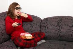 Liten flicka som håller ögonen på tv 3d och äter donuts Arkivfoto